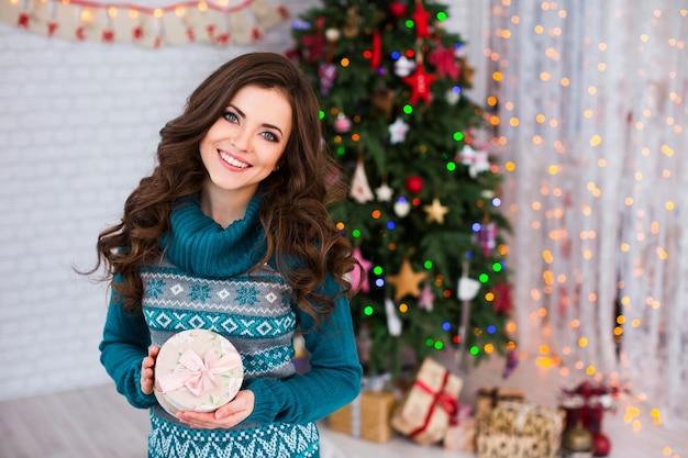 Schöne frau halten weihnachtsgeschenk neben weihnachtsbaum. geschenke für das neue jahr und weihnachten geben.