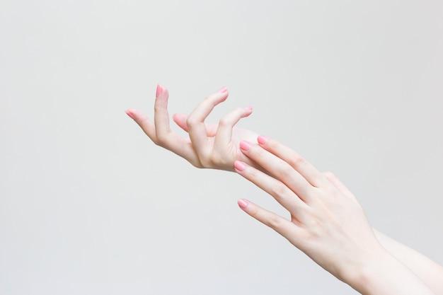 Schöne frau hand weibliche hand auftragen von lotion oder handcreme zur handpflege im spa und maniküre