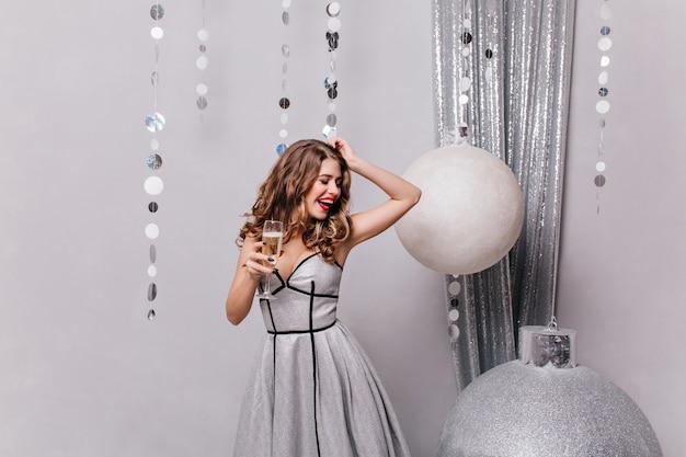 Schöne frau hat süßes aussehen und freut sich über bevorstehende feiertage, tanzt gegen weihnachtsspielzeug
