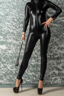 Schöne frau herrin im latexbodysuit steht nahe wand, die eine peitsche hält