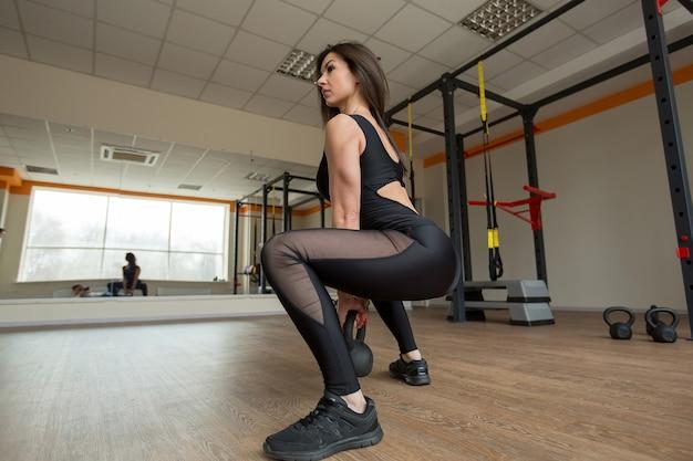 Schöne frau hockt mit kettlebell im fitnessstudio