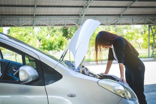 Schöne frau, ihr auto ist kaputt während sie zur arbeit im büro eilte