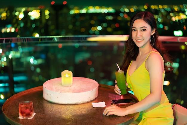 Schöne frau im abendkleid, das cocktail am restaurant über nacht stadt hält