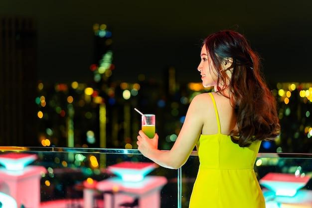 Schöne frau im abendkleid, das cocktail über nachtstadt hält
