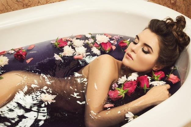Schöne frau im bad mit blumen