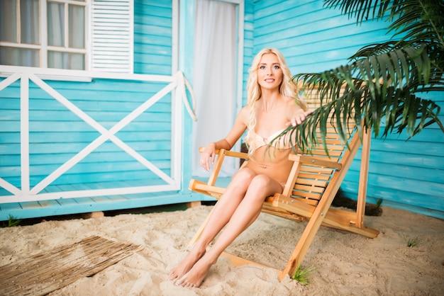 Schöne frau im badeanzug auf sonnenliege liegend