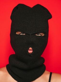 Schöne frau im badeanzug der schwarzen badebekleidung. modell mit banditen-sturmhaubenmaske.