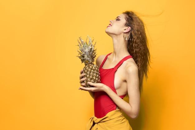 Schöne frau im badeanzug mit ananas in der hand
