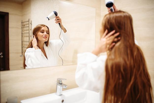 Schöne frau im bademantel, die haare mit trockner gegen spiegel im badezimmer trocknet, morgenhygiene, schönheitspflege