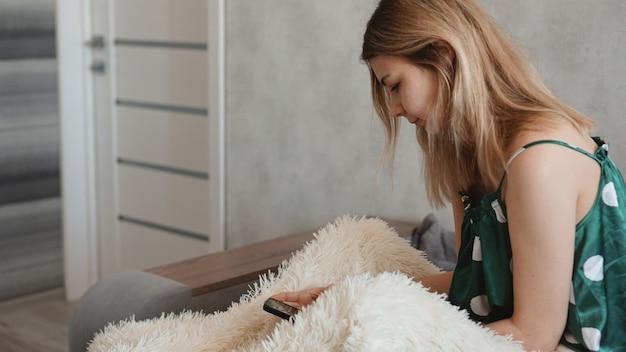 Schöne frau im bett mit ihrem smartphone zu hause im schlafzimmer