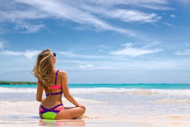 Schöne frau im bikini am tropischen strand. das mädchen sitzt mit dem rücken zur kamera im sand und schaut auf den ozean.