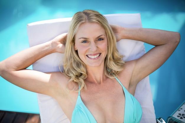 Schöne frau im bikini, der auf einem sonnenruhesessel sich entspannt