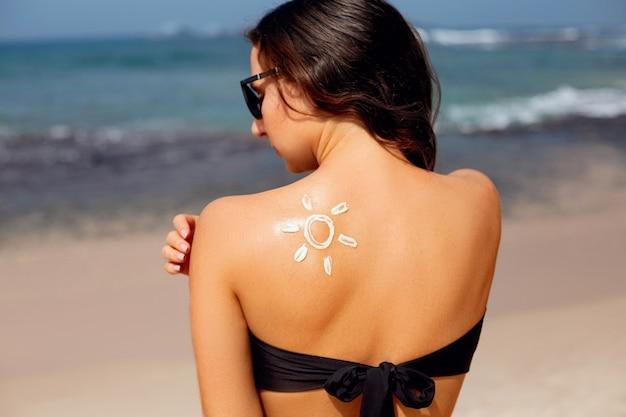 Schöne frau im bikini, die sonnencreme auf gebräunter schulter anwendet. sonnenschutz.