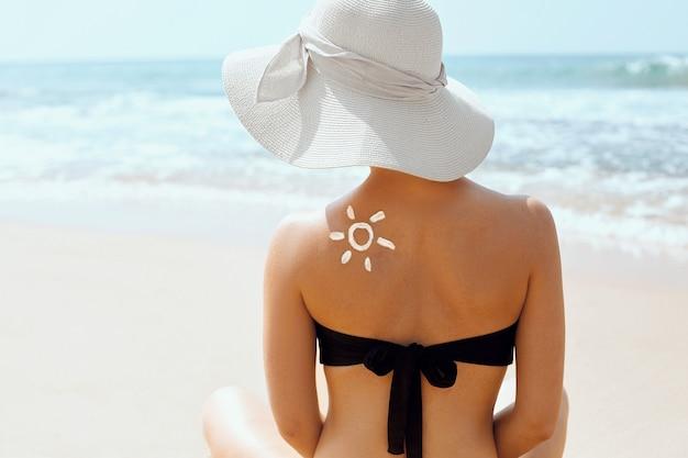 Schöne frau im bikini, die sonnencreme auf gebräunter schulter anwendet.
