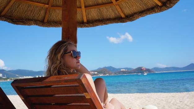 Schöne frau im bikini genießt die tropische sonne für eine bräune auf einem liegestuhl an einem tropischen strand in china