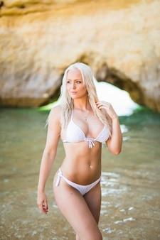 Schöne frau im bikini. junges und sportliches mädchen, das an einem strand im sommer aufwirft