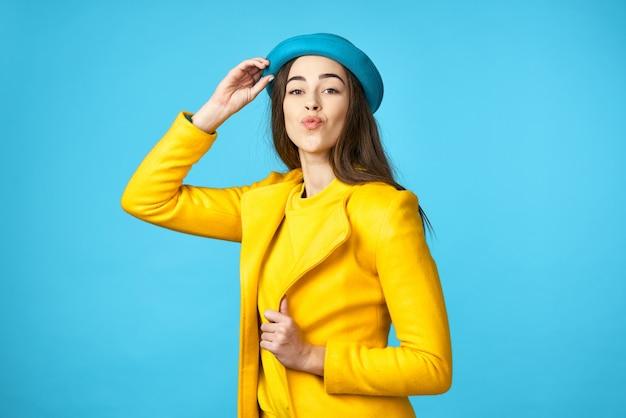 Schöne frau im blauen hut und im gelben mantel