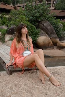 Schöne frau im boho-kleid, das nahe luxusresort aufwirft. genießender urlaub auf tropischer insel.