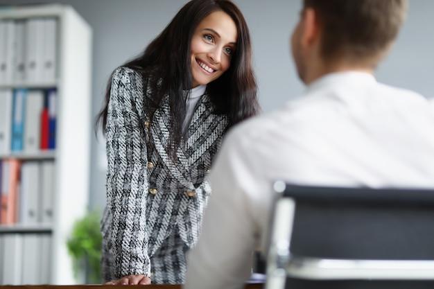 Schöne frau im büro kommuniziert freundlich mit einem mann