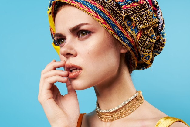 Schöne frau im bunten turban attraktiven blick schmuck lächeln blauen hintergrund