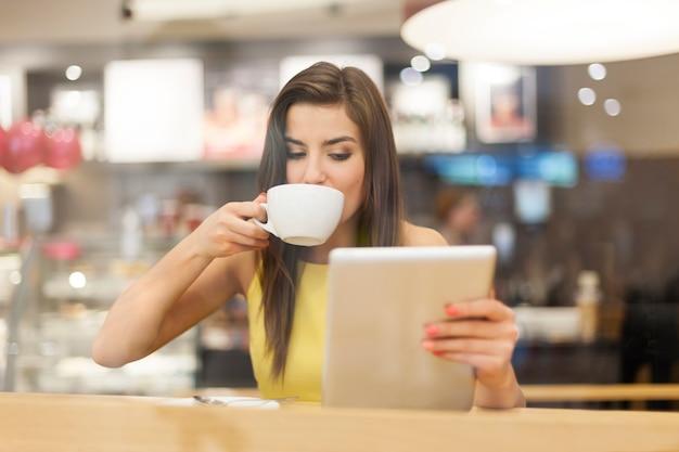 Schöne frau im café mit digitaler tablette
