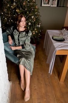 Schöne frau im eleganten kleid auf dem hintergrund des luxusweihnachtsbaums in einem raumreichen innenraum