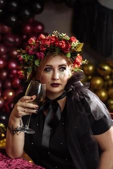 Schöne frau im eleganten schwarzen kleid mit einem glas wein, das geburtstag feiert, halloween