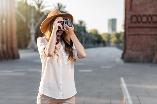 Schöne frau im entdecker-outfit, das mit weinlesekamera reist und fotos macht.