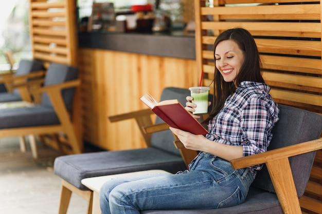 Schöne frau im freien straße sommer café holzcafé sitzt in freizeitkleidung, buch mit tasse cocktail lesen?
