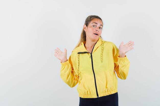 Schöne frau im gelben regenmantel, der idk geste zeigt und verwirrt schaut