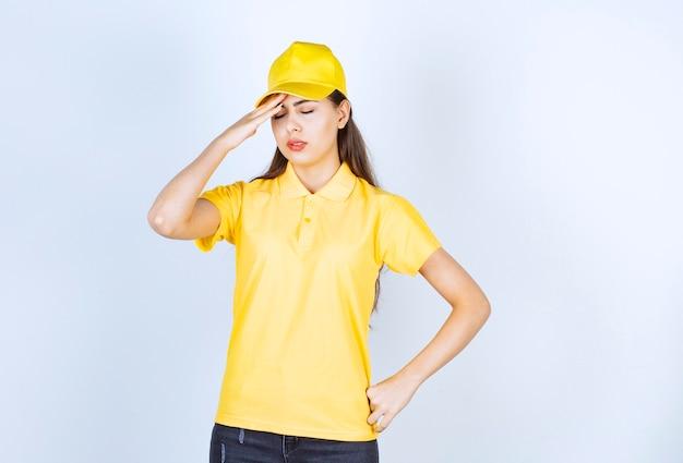 Schöne frau im gelben t-shirt und in der kappe, die auf weißem hintergrund deprimiert ist.