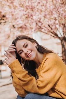Schöne frau im hellen pullover, der auf straße gegen hintergrund von sakura aufwirft. stadtporträt der attraktiven dame im gelben outfit breit lächelnd