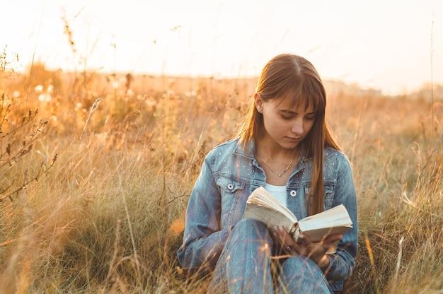 Schöne frau im herbstfeld, die ein buch liest. die frau sitzt auf einem gras und liest ein buch. ruhe und lesen. lesen im freien.