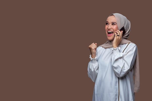 Schöne frau im hijab bekommt die gute nachricht mit einem schreienden gesichtsausdruck auf ihrem handy