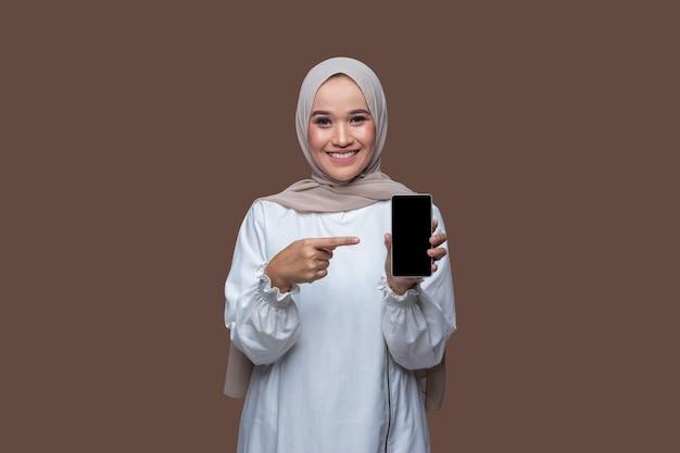 Schöne frau im hijab hält ein handy und zeigt mit einem lächeln auf den telefonbildschirm