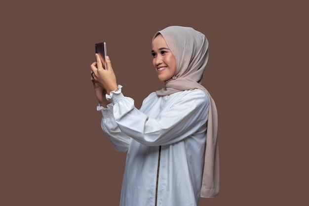 Schöne frau im hijab ist bei videoanruf mit handy