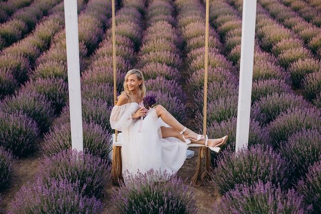 Schöne frau im hochzeitskleid im lavendelfeld