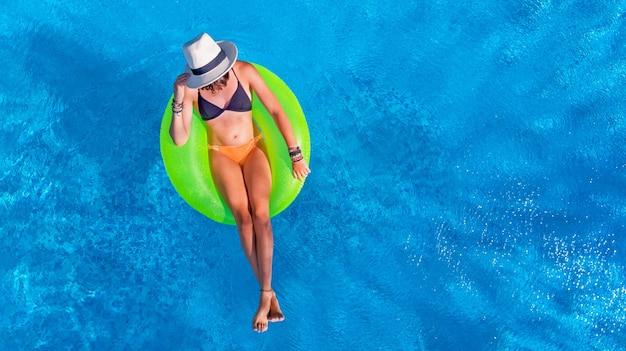 Schöne frau im hut im schwimmbad auf aufblasbarem ring im wasser im urlaub