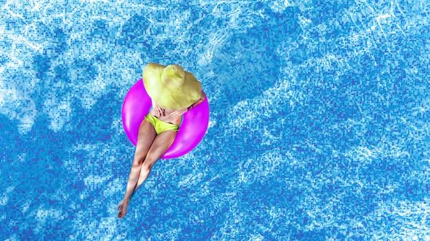 Schöne frau im hut im schwimmbad-luftbild von oben, junges mädchen im bikini entspannt und schwimmt auf aufblasbarem ringkrapfen und hat spaß im wasser im familienurlaub, tropischer ferienort