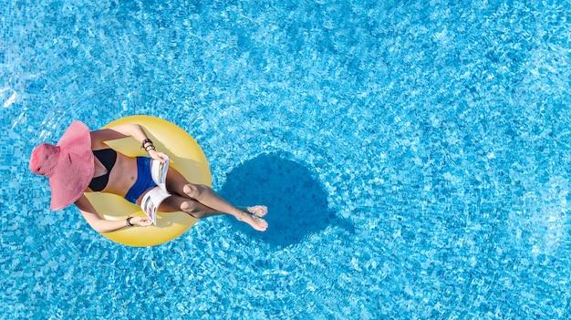 Schöne frau im hut in der luftansicht des schwimmbades von oben, junges mädchen im bikini entspannt und schwimmt auf aufblasbarem ringkrapfen und hat spaß im wasser, tropischer ferienort