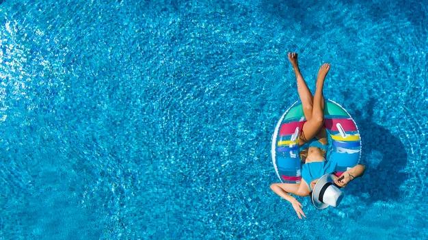 Schöne frau im hut in der luftansicht des schwimmbades von oben
