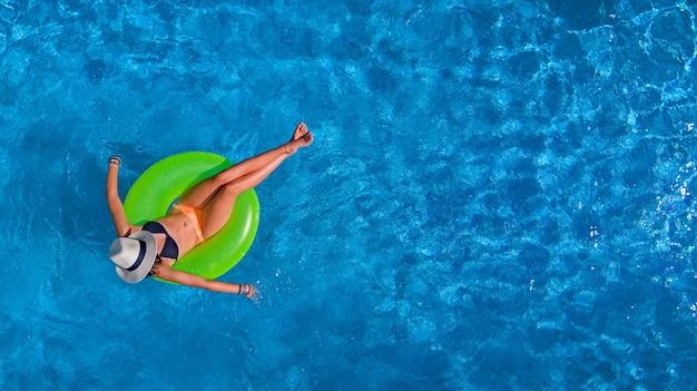 Schöne frau im hut in der luftaufnahme des schwimmbades von oben, junges mädchen im bikini entspannt und schwimmt auf aufblasbarem ringkrapfen und hat spaß im wasser im urlaub