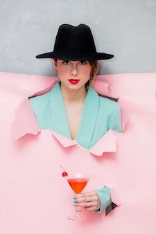 Schöne frau im hut und in der blauen klassischen jacke mit martini-glas