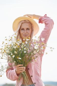 Schöne frau im hut und mit einem korb der feldgänseblümchen im sonnigen sommertag.