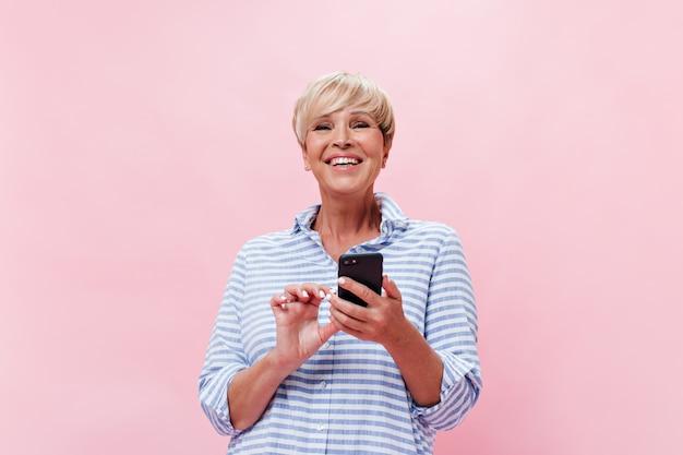 Schöne frau im karierten hemd posiert glücklich auf rosa hintergrund und hält smartphone