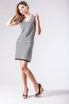 Schöne frau im kleid elegantem. modell in modischer kleidung auf einer hellen oberfläche