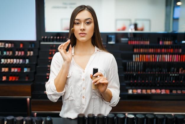 Schöne frau im kosmetikladen, vorderansicht. käufer an der vitrine im luxus-beauty-shop-salon, kundin im modemarkt