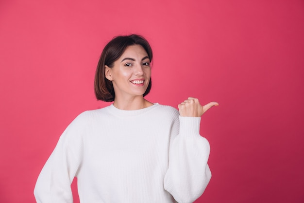 Schöne frau im lässigen weißen pullover an der roten wand