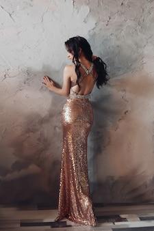 Schöne frau im langen goldenen kleid steht zurück zur kamera