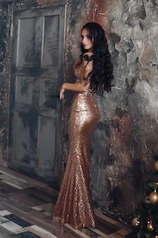 Schöne frau im langen goldenen kleid tritt zurück und schaut zur kamera